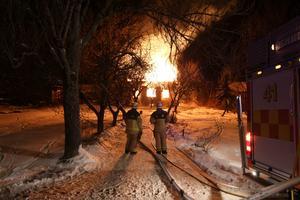 Två brandmän bevakar lågorna när villan tillåts brinna ner.