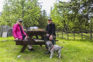 Alice och Gunnar Ohlander sitter och fikar tillsammans med hunden Smilla.
