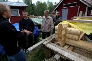 Knuttimmer. Daniel Lindblom, Richard Bergeå, Lennart Magnusson och Kalle Vestergren pratar timringsteknik vid Richards påbörjade timmerhus.