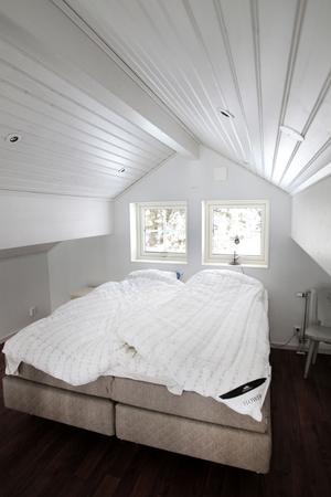 Sängen uppe på loftet under det V-formade taket med inbyggda spotlights.