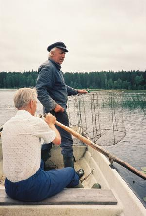 Sven Bovin och Björn Pettersson lägger i en mjärde i Mörttjärn. En av de små skogssjöarna som finns i norra Västmanland. Mindre gäddor och små abborrar var ofta resultatet när vi vittjade mjärden.