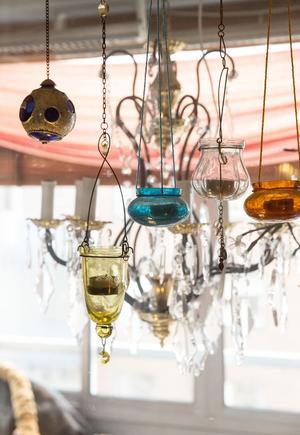 Förutom lampor hänger ljuslyktor i olika färger på rad i fönstret.