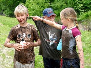 Elin Sundberg torka bort leran ur Dennis Bufvers öra efter fotbollskamp på en myr. Bakom står Mårten Vänn.