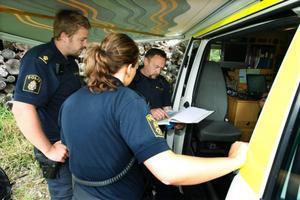 Insatsledaren Kjell Johansson, längst till höger, visar poliserna Anders Sundstedt och Hanna Fagerström nya sökområden.