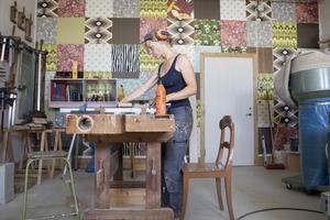 Ena kortsidan i verkstaden täcks av färgglada plattor för att skapa ett hemtrevligare intryck.