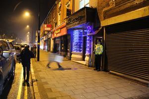 En polisman vaktar porten på en adress i Birmingham tidigt på torsdagsmorgonen. Beväpnad polis slig till mot lägenheten under natten.