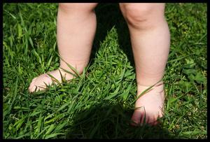 Min dotters små fötter trampar runt i gräset för första gången.