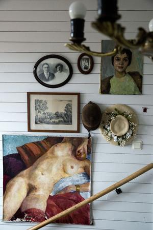På en vägg i trappen hänger farmors gamla hatt, Mikaelas första ridhjälm, porträtt på paren som tidigare bott i huset och några målningar av Mikaelas morfars  fars far. Den nakna kvinnan har hängt på flera ställen i huset, och ibland skärrat besökare. I hallen generar den nog minst, tror Mikaela.