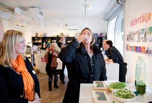Annika Jonsson testar en vetegräsdrink. Linda Färggren på Södertäljebyrån ser glatt på.