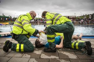Ambulanspersonalen utövar första hjälpen på en av Lugnets simlärare. Den årliga livräddaruppvisningen för årskurs 2 och årskurs 3, på Lugnets friluftsbad.