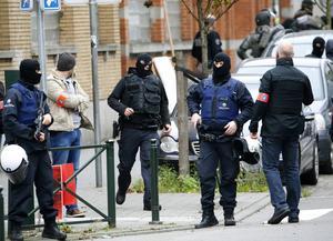 Belgisk polis genomför ett tillslag i stadsdelen Molenbeek i sökandet efter misstänkta islamister med kopplingar till terrordåden i Paris.