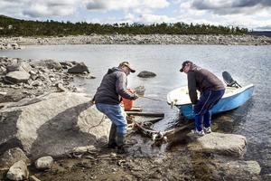 Jan Åke Johansson och Rolf Bergvall hjälps åt att dra upp en båt på den eroderade stranden nedanför samebyn i Stora Stensjön.