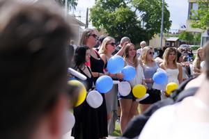 Ballonger i blått och gult släpptes mot himlen efter mösspåtagningen.