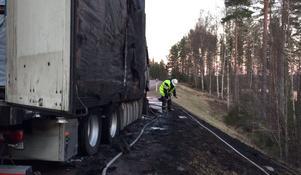 En brandman skyfflar lerig aska vid olycksplatsen.