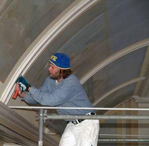 Lennart Persson. Skrapar bort målarfärgen för att få fram de uråldriga målningen som gömmer sig under. Foto: Sandra Mattsson