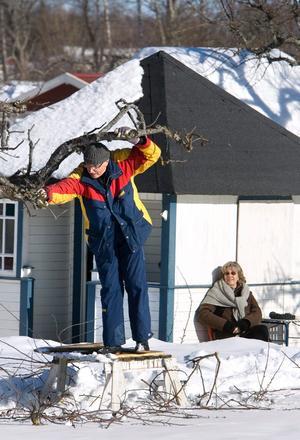 Agne Strindlund asar trädet i CV:s koloniträdgård medan Margareta lapar sol.