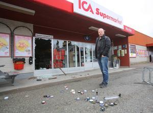 Peter Eriksson framför den krossade rutan till butiken.
