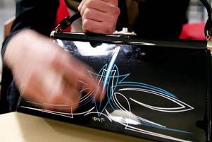 Nygammalt. Färgen är ny men designen på burkarna andas lika mycket 50-tal som själva målningen.Säker. Thomas Sigvardsson målar sina smala symmetriska ränder helt på fri hand. Och han har aldrig målat fel.