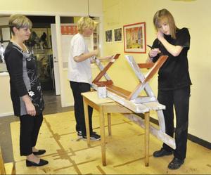 Läraren Märta-Stina Gahlin tittar på när Andreas Sjödin och Lina Holmgren målar kyrkbänkar som ska återvinnas.