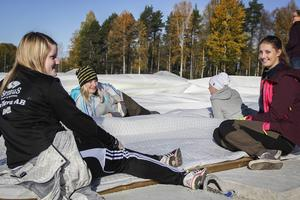 Malin Ljus, Alexandra Larsson, Emilia Persson och Madeleine Olsson från Tallåsens IF håller halltakets sida på plats medan isoleringen svetsas fast.