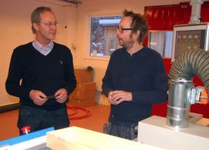 Johan Mårtensson vid Bengt Slöjdare, till höger i bild, berättar för näringslivschefen Bengt Erik Lundborg hur den nya tryckpressen fungerar.