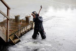 Fredrik Wesemeyer hjälper till att hugga upp ett hål i isen inför kvällens Kulturbastu.