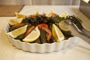 Vinbladsdolmarna serveras med citron. Det finns kalla vegetariska varianter och varma med kött.