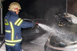Räddningstjänsten ser till att branden i bilen verkligen är släckt.