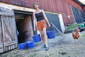 TÖRSTSLÄCKARE. Maria Brook bär iväg med vatten till getterna i hägnet hemmavid.