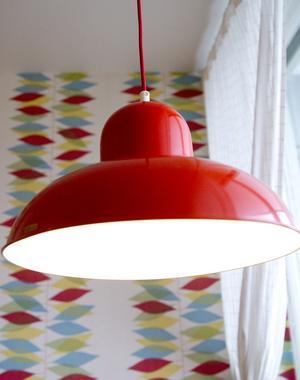 Den röda kökslampan i plåt sitter ovanför köksbordet, och även här går färgen igen i tapeten.