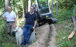 Alf Jakobsson och Björn Falkeström, här tillsammans med hunden Love, är glada att arbetet med att gräva för fiber i Ingvallsbenning, Turbo och Prästhyttan äntligen kommit i gång. Foto: Eva Langefalk/DT
