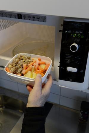 Matlåda med rester ställs in i en mikrovågsugn och värms upp – en vanlig syn på alla arbetsplatser. Men hur mycket kemikalier hamnar egentligen i maten ...? Foto: Jessica Gow/TT