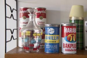 I stringhyllan i köket samsas fina loppisfynd. Vaniljsocker- och bakpulverburkarna används, Karoline har fyllt dem med rätt innehåll.