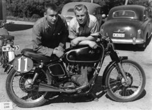 Hedemoras TT- och motocrossförare Rolf Carlsson, t v, och Eije Widén poserar tillsammans med SMK Hedemoras TT-hoj av märket AJS 7R.