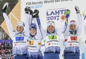 Sveriges Stina Nilsson, Ebba Andersson, Charlotte Kalla och Anna Haag jublar på podiet vid blomsterceremonin.