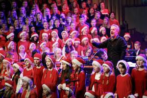 Dirigenten Joakim Unander leder inte bara kör och orkester. Här vänder han sig till publiken för allsång i Nu tändas tusen juleljus.