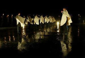 I vita cèper framfördes lugn och stilla dans till dov musik. Regnet hade slutat strila och mörkret lagt sig.