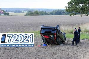 På åkern. Den voltande bilen landade på taket en bit ut på en åker, här inspekteras bilen av polis.