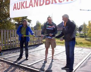 Kommunalrådet Peter Helander, till vänster och Rolf Hammar, till höger, assisterar Jörgen Aukland när han inviger sin
