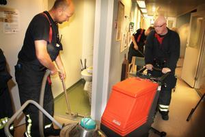 Nicke Kardell och Magnus Lindhé suger upp vatten med vattendammsugare i korridoren.