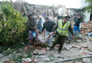 En polis och tre civilpersoner hjälper till att bära ut en kropp från ett rasat hus i Talca.