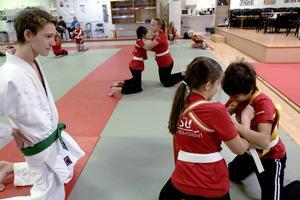 Elias Öberg instruerar ett gäng ungdomar som prövar på judo.