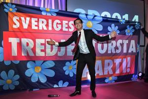 Partiledaren Jimmie Åkesson framför en banderoll med texten
