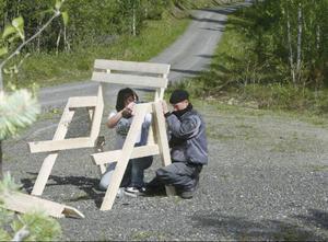 """Marcel Hein och René Brödnev jobbar mitt i storskogen med sina stolar till jämtländska älgpass. 40 stolar har de tyska ungdomarna byggt. Under två dagar kånkar de ut stolarna till förutbestämda älgpass. """"Det här blir nog ett bra pass"""", säger René och gör en provskjutning."""
