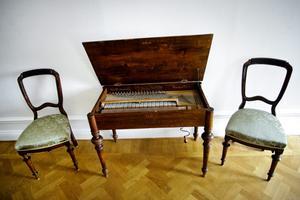 Det självspelande pianot är till vardags ett avställningsbord. Stolarna stämmer bra i stilen, men är köpta på annat håll.