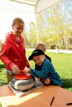 """Tunga gissningar. Vad väger stenen som Lindesbergs curlingklubb hade med sig? Den frågan ville bröderna Leo, 6 år, och Lukas, 4 år (som här lyfter stenen), besvara. """"Vi gissade på runt 35-40 kilo"""", säger Emmy Westerberg. Foto: Adam Söder"""