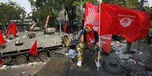 Spåren efter lördagens demonstrationer är påtagliga i den thailändska huvudstaden. Här sitter en rödrocksanhängare på ett övergivet arméfordon.