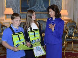 Drottning Silvia köpte på fredagen årets första majblomma från femteklassarna Axel Stridsberg och Ella Bosell från Solskiftesskolan i Åkersberga vid en ceremoni Stockholms slott. Drottningen är majblommans högsta beskyddare.