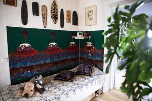 I hallen får det plats med en säng. Afrikanska masker pryder väggen och tyget på väggen är från Kenya.
