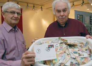 Claes Höglund och Arne Böhlmark visar upp ett kort med poststämpeln för Frimärkets dag i Mora.